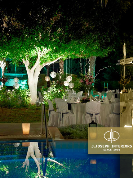 Outside venue with chairs and many plants, trees and a pool.