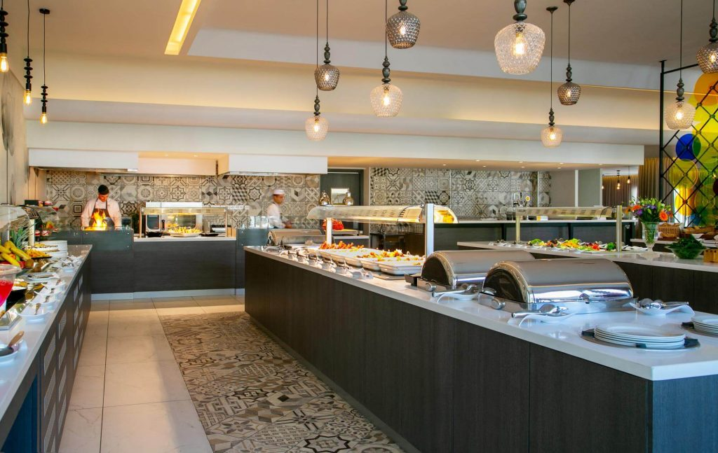 The hotel's buffet with various dishes and some cooks.