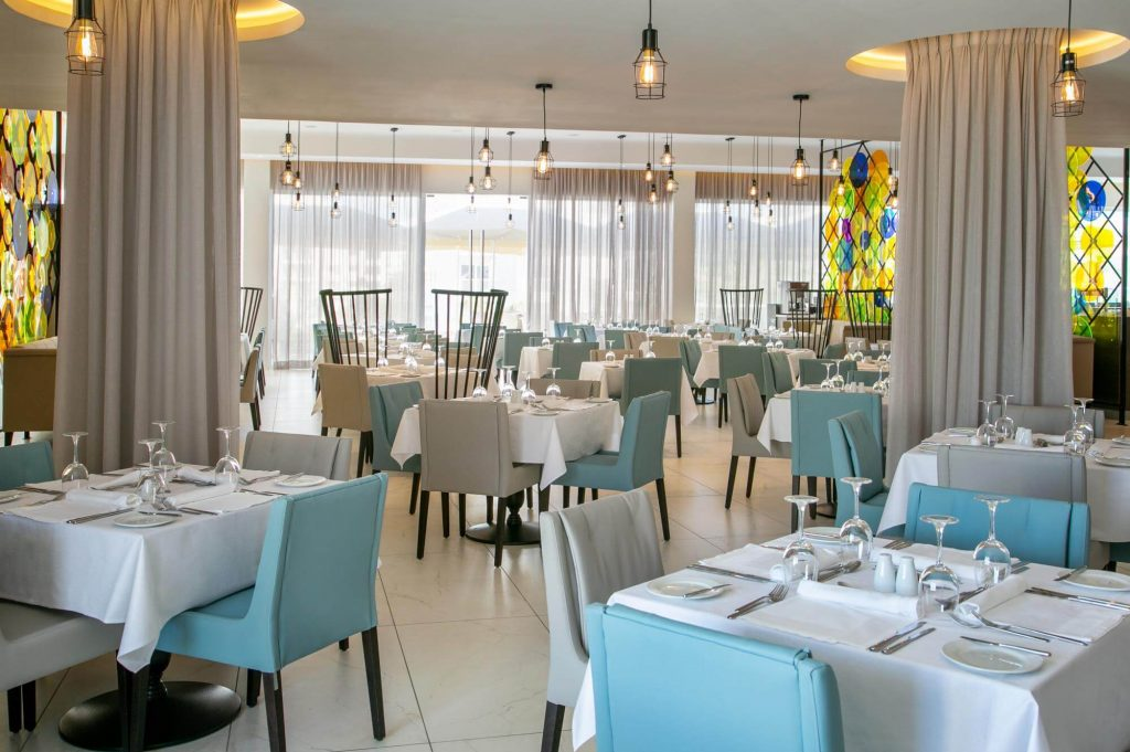 The interior of the hotel with many lights, many white and blue chairs and cutlery and glasses at the tables.