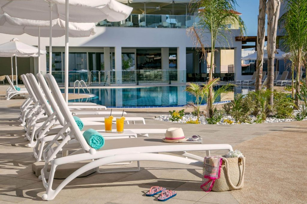 Poolside of Vaggelis hotel, with pool chairs, umbrellas, two glasses of juice, and plants.