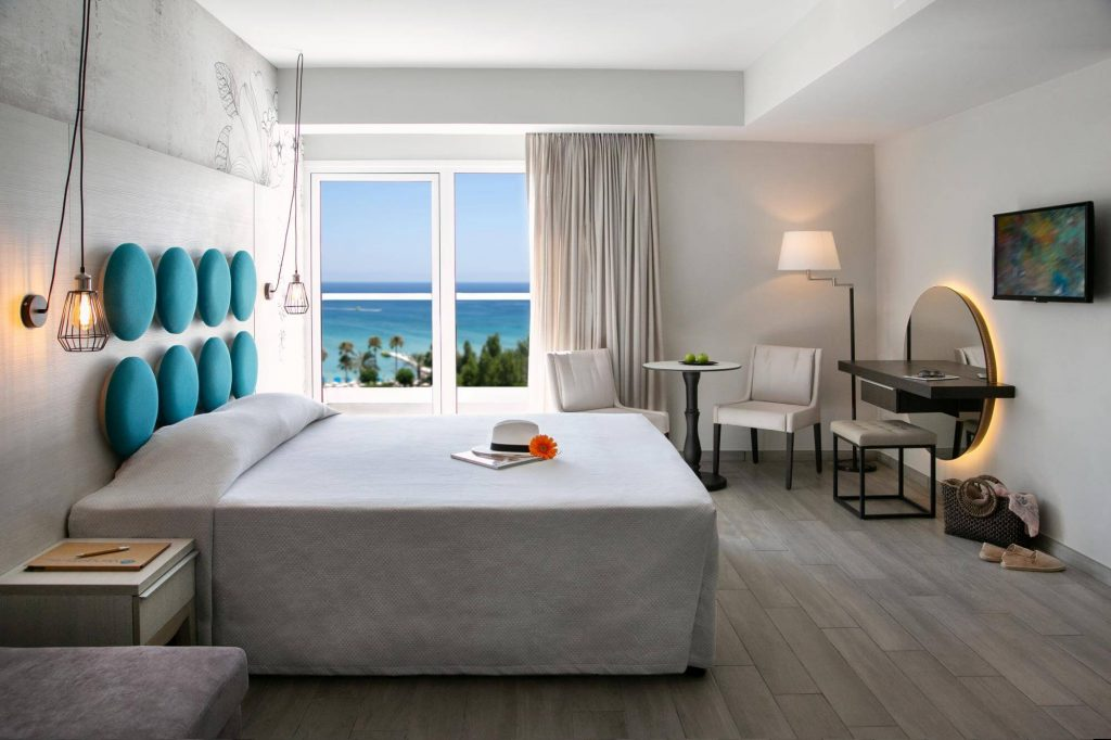 Interior of one of the bedrooms in Vaggelis hotel, with a big bedroom, sea view, two white chairs, a small table, a mirror and a tv.