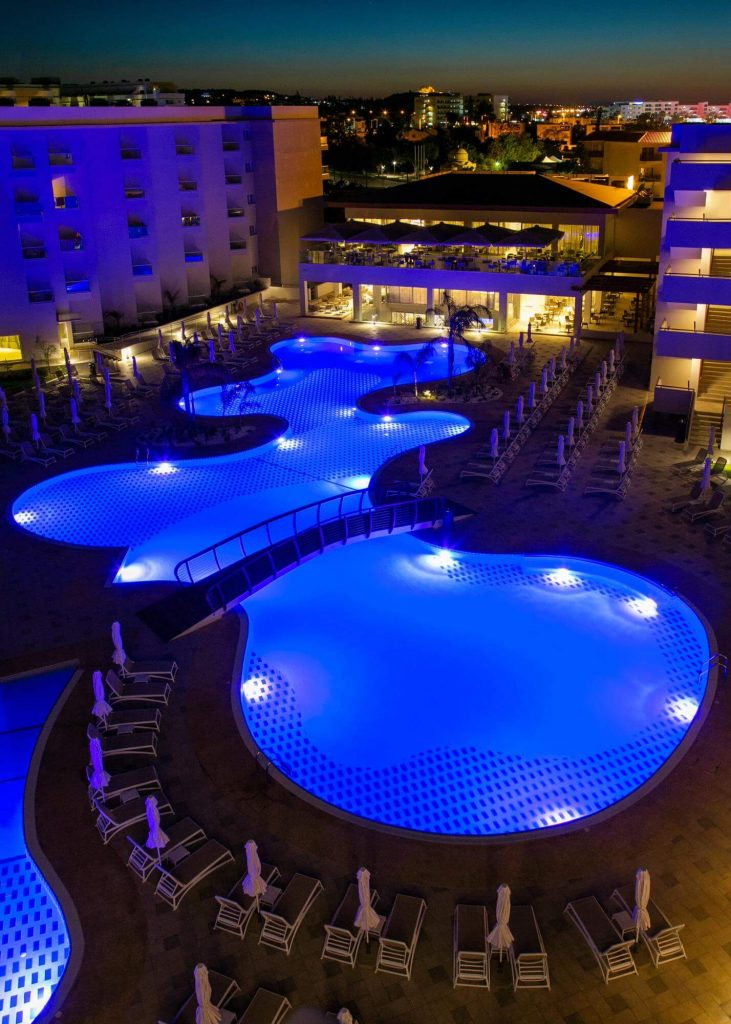 Night reception of the hotel's outdoor area, from the pool view.