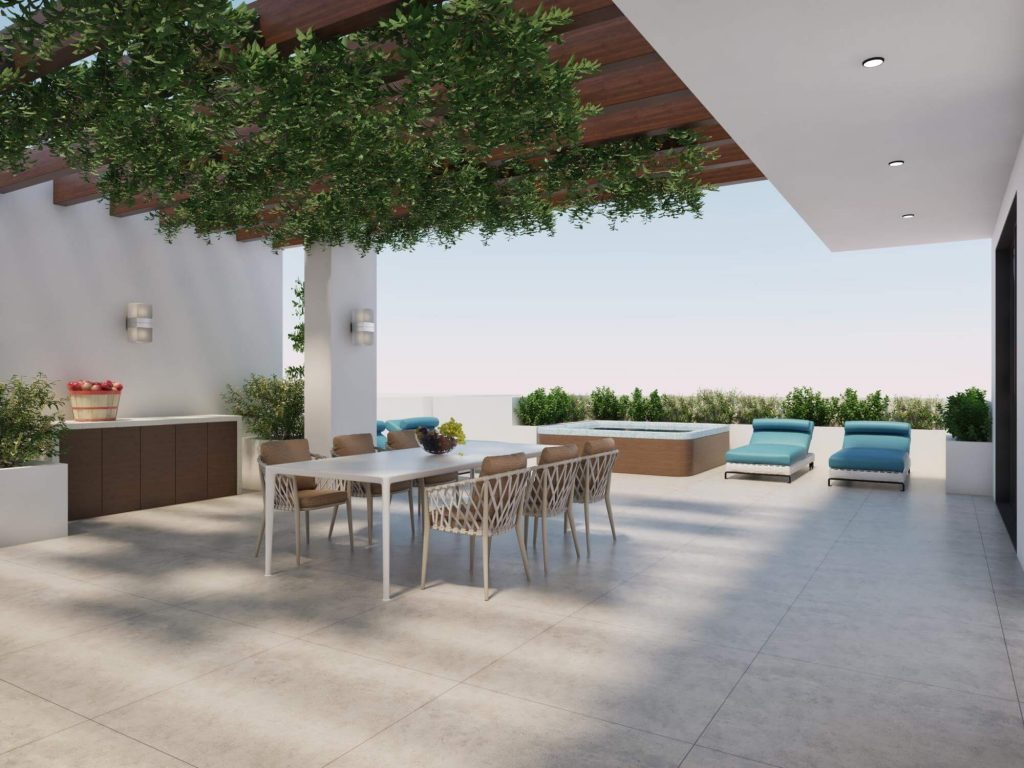 Poolside with table, six chairs, pool loungers and plants.