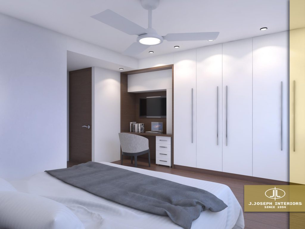 Bedroom with white walls, white cupboard, wooden desk and door.