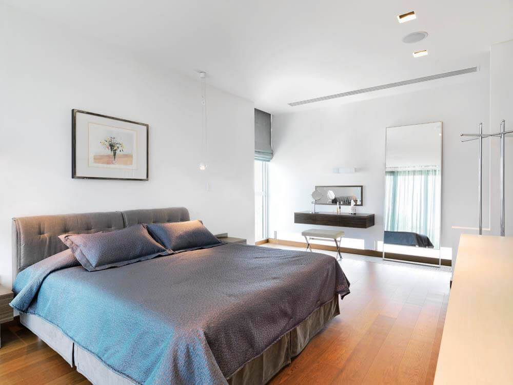 Bedroom In the colors of the gray, with a big bed, a full body mirror and a painting on the wall.