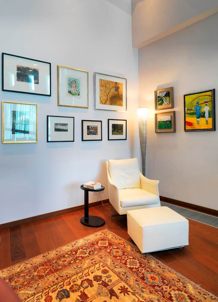 Corner with a carpet, a lamp, a white chair and ten paintings on the wall.
