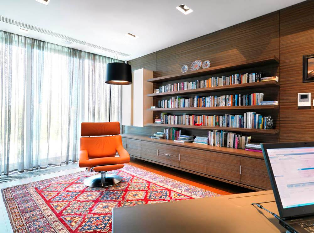 Room with desk, an orange chair, and a wooden library furniture.